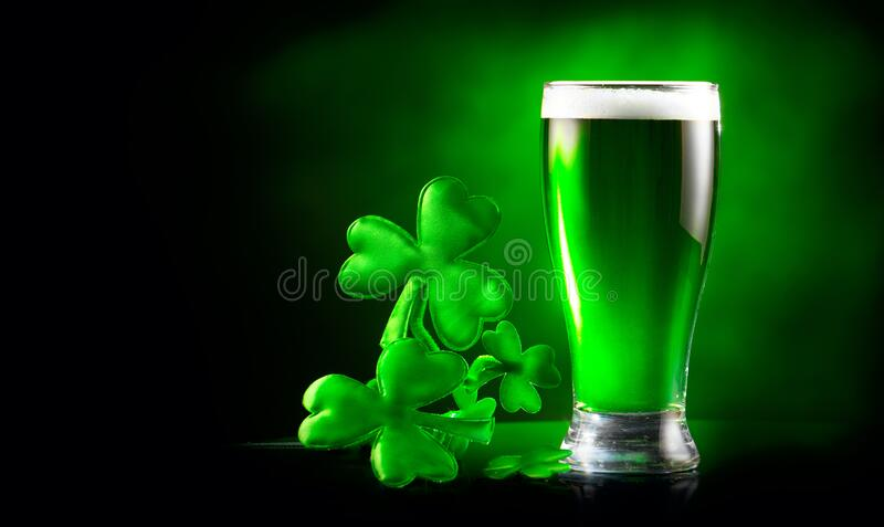St. Patrick`s Day Green Beer pint over dark green background, decorated with shamrock leaves. Glass of Green beer close-up royalty free stock image