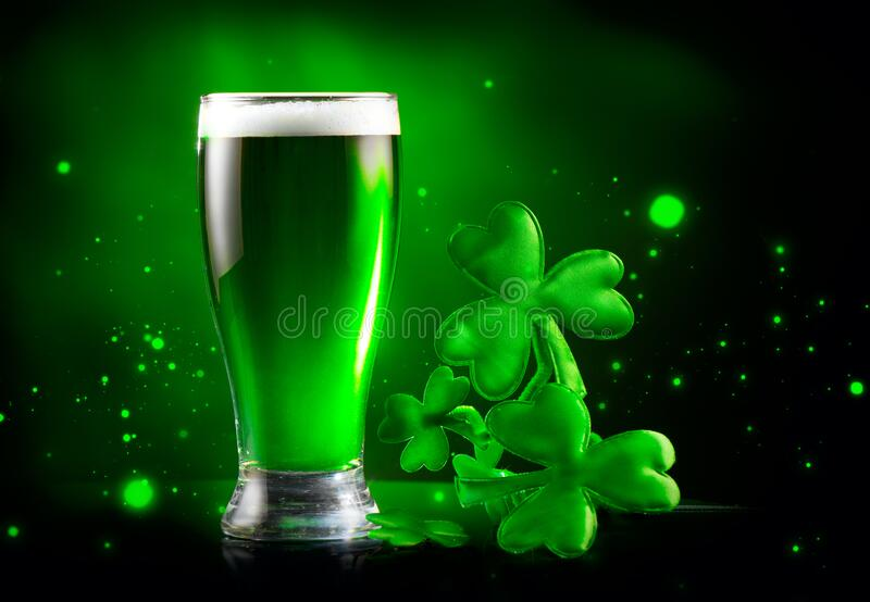 St. Patrick`s Day Green Beer pint over dark green background, decorated with shamrock leaves. Patrick Day Irish pub party royalty free stock photos