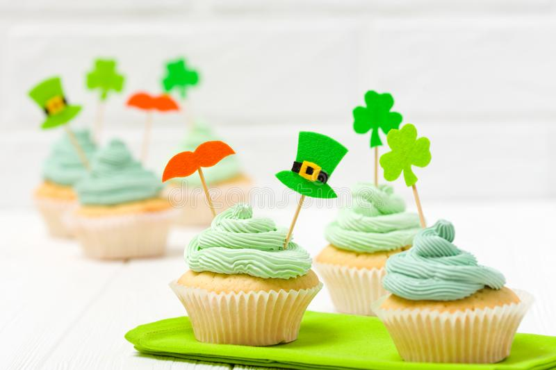 St. Patrick`s Day theme colorful horizontal banner. Cupcakes decorated with green buttercream and craft felt decorations in form royalty free stock photography