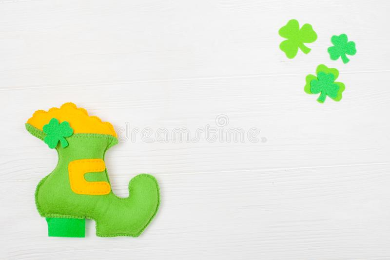 St. Patrick`s Day theme colorful horizontal banner. Green leprechaun hand made shoe with gold and shamrock leaves on white wooden. Background. Felt craft royalty free stock images