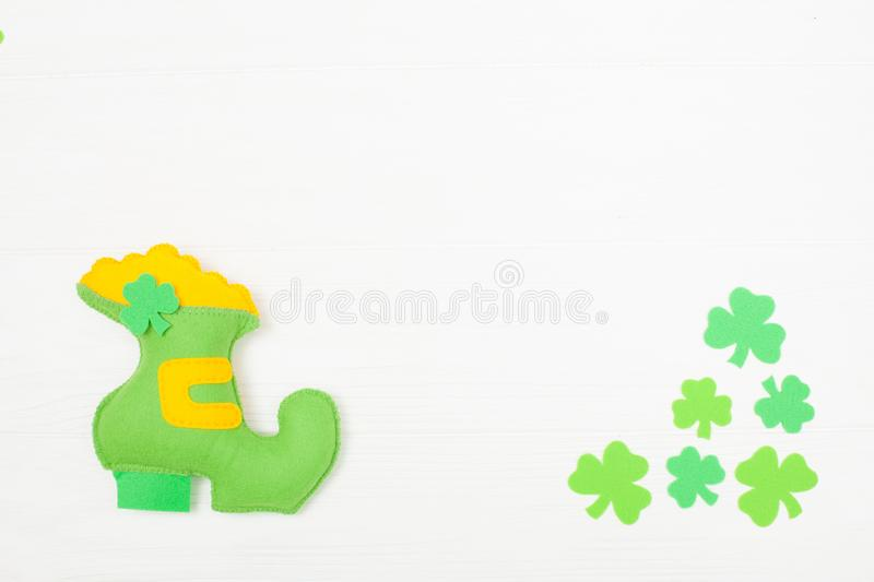 St. Patrick`s Day theme colorful horizontal banner. Green leprechaun hand made shoe with gold and shamrock leaves on white wooden stock images