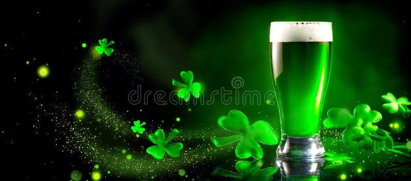 St Patrick ` s Tag Grünes Bierhalbes liter über dem dunkelgrünen Hintergrund, verziert mit Shamrock verlässt lizenzfreies stockbild