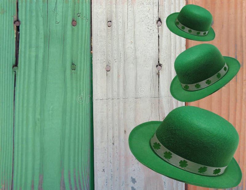 St Patrick Tageshintergrund von fallenden Kobold-Hüten gegen irische Flaggen-Farben lizenzfreie stockfotografie