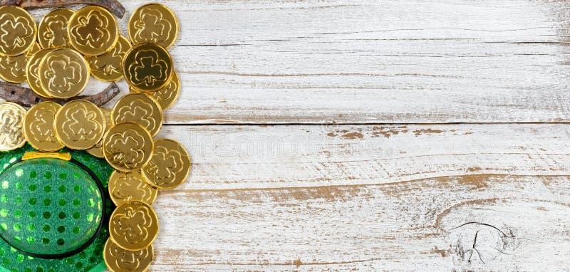 St Patrick złoto z kapeluszem na nieociosanym białym drewnianym tle zdjęcia stock