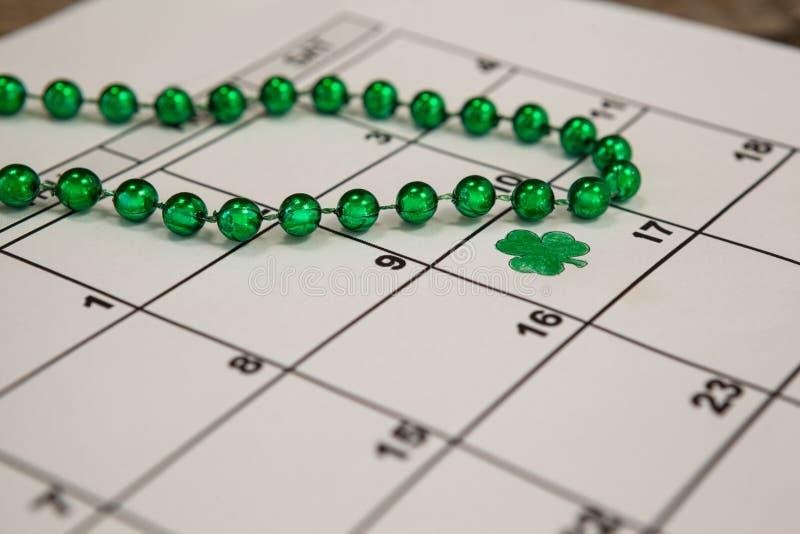 St Patricks天三叶草和小珠在日历保持了 库存图片