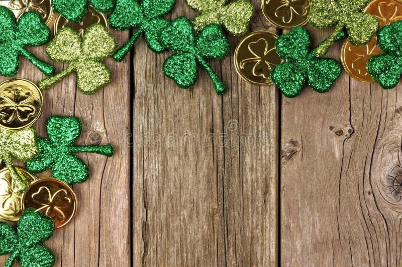 St Patricks Day decor corner border over rustic wood. St Patricks Day corner border of shamrocks and gold coins over a rustic wood background stock photos