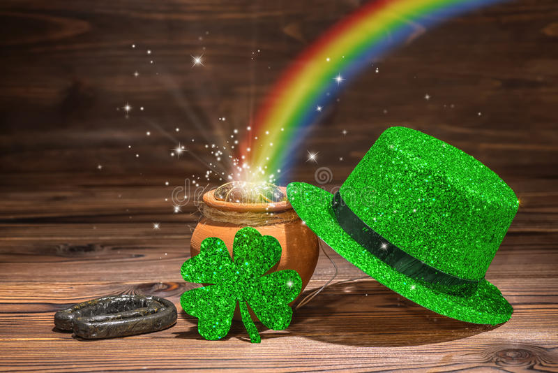 St Patricks day decoration with magic light rainbow pot full gold coins, horseshoe, green hat and shamrock on vintage wooden back stock photo
