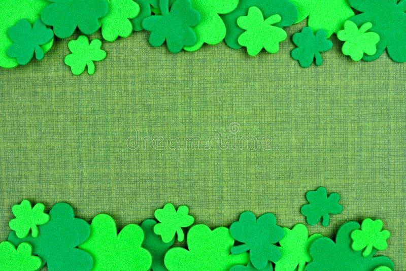 St Patricks Day double border of shamrocks over green linen royalty free stock photo