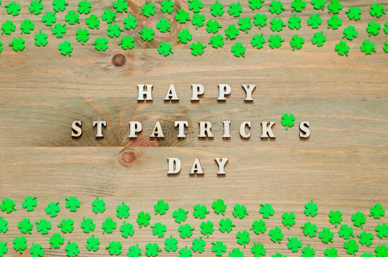 St Patricks Day festive background. Green quatrefoils on the wooden background and inscription Happy St Patrick`s day royalty free stock images
