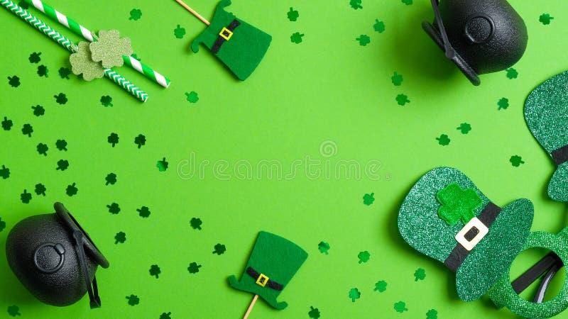 St Patricks Day frame of leprechaun hats, pots of gold, drinking straws, Patricks Day glasses on green background. Saint Patrick. 's day party invitation royalty free stock photos