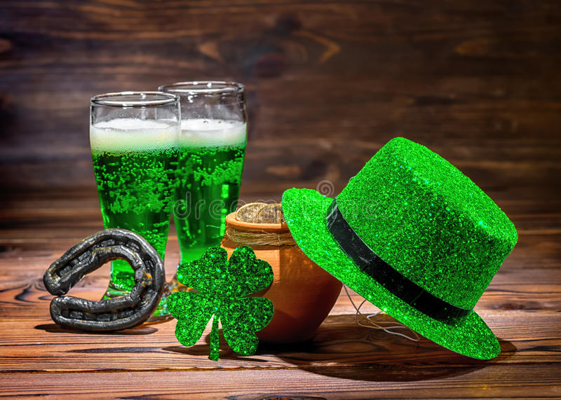 St Patricks day with glasses of green beer, leaf clover, leprechaun hat, horseshoe and pot full gold coins on vintage wooden back stock images