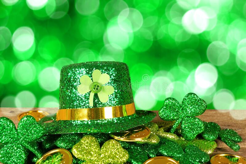 St Patricks Day leprechaun hat on a pile of gold coins and shamrocks with twinkling green background stock image