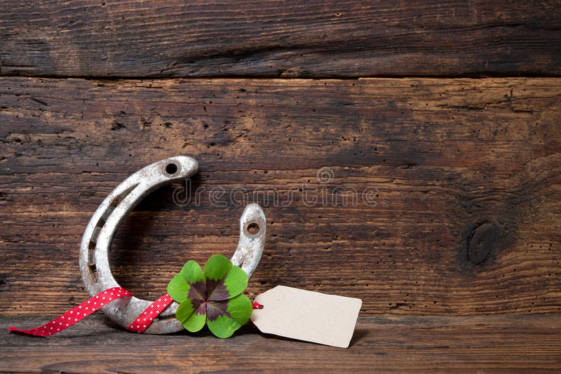 St. Patricks day, lucky charms. Four leaved clover and a horseshoe on wooden board stock photo