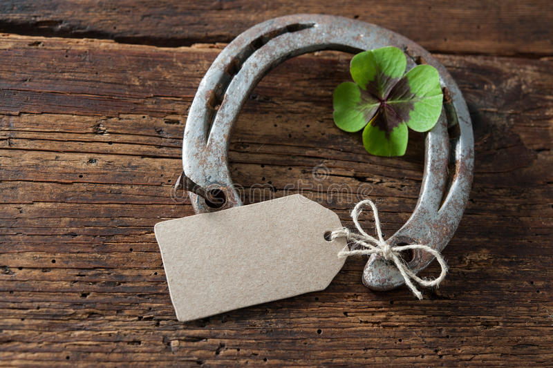 St. Patricks day, lucky charms. Four leaved clover and a horseshoe on wooden board stock photos
