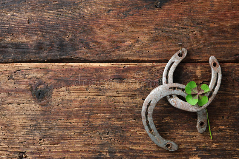 St. Patricks day, lucky charms. Two horseshoes with a four leaved clover on wooden board stock photography