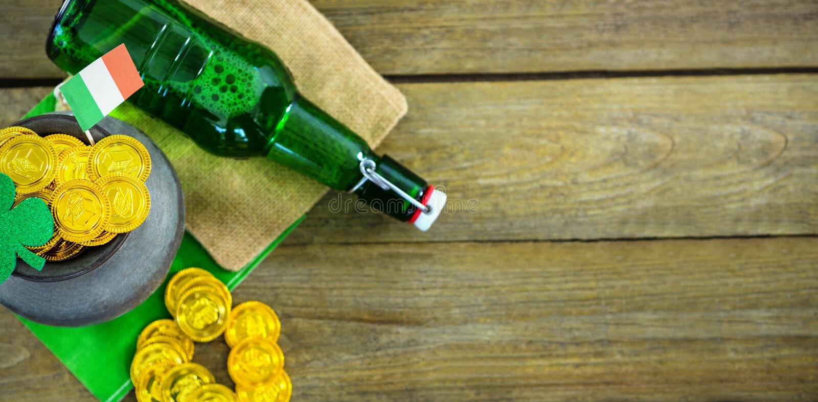 St Patricks Day shamrock with flag and beer bottle by pot filled with chocolate gold coins stock images