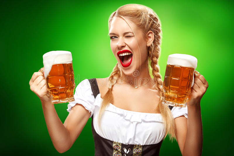 St Patricks Day. Young Oktoberfest waitress, wearing a traditional Bavarian dress, serving big beer mugs on blue stock photography