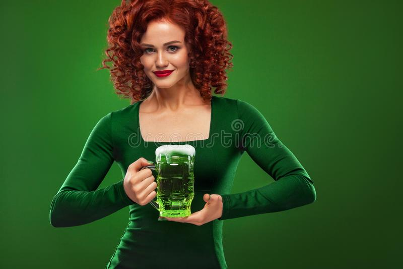 St Patricks Day. Young and redhead Octoberfest waitress, wearing a dress, serving big beer mugs on green background royalty free stock images