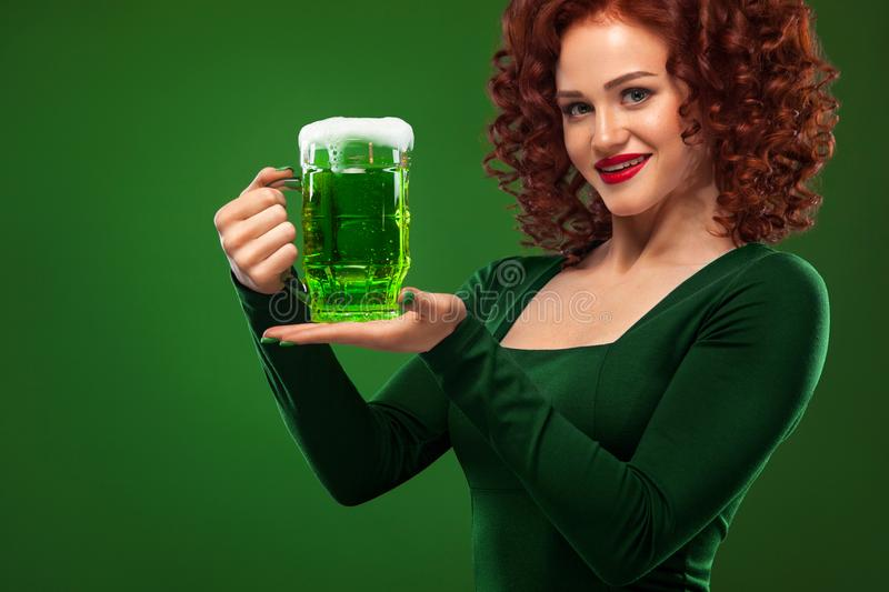 St Patricks Day. Young and redhead Octoberfest waitress, wearing a dress, serving big beer mugs on green background stock photos