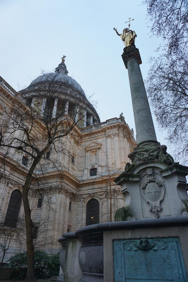 St Paul`s Cathedral from a low angle with statue in foreground royalty free stock photo