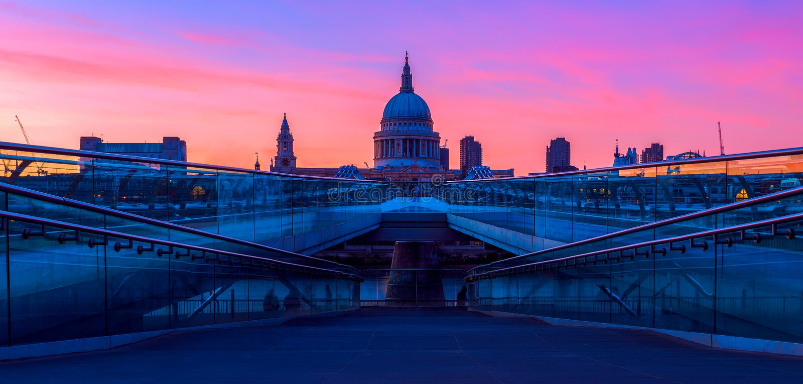 St Paul's Cathedral and the Millennium Bridge in London. Panoramic view of purple sunset at St Paul's Cathedral and the Millennium Bridge in London stock photos