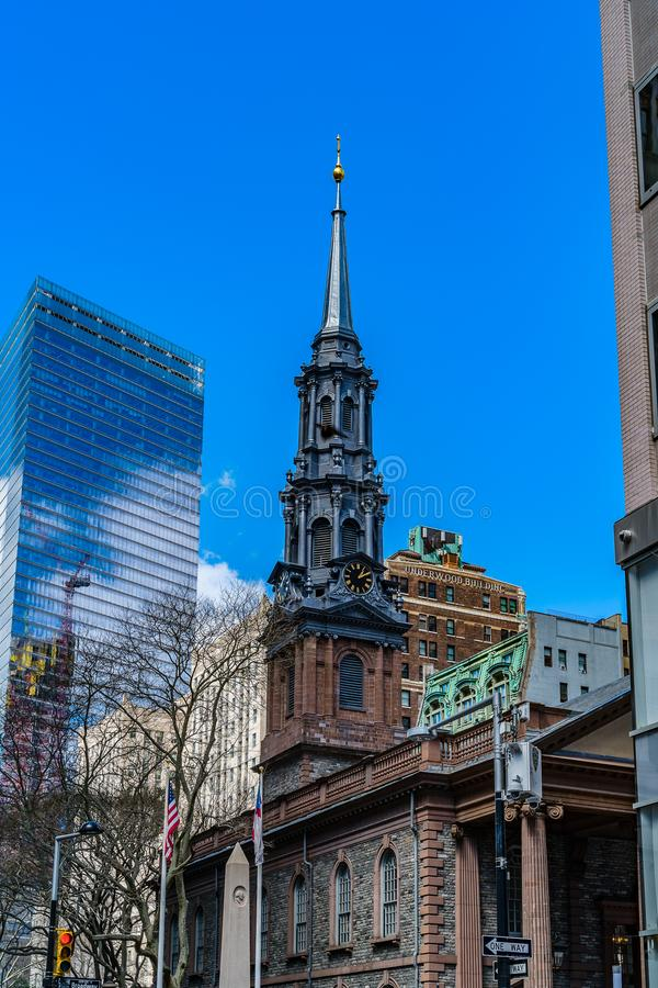 St. Paul`s Chapel of Trinity Church Wall Street in the background is Seven World Trade Center with clouds and construction crane royalty free stock photos