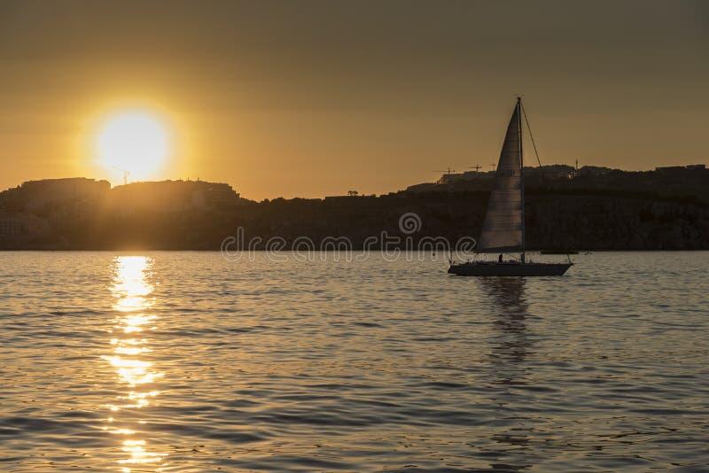 St Pauls Bay Malta della barca a vela di tramonto immagini stock libere da diritti