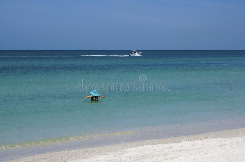 St. Pete Beach, Florida April 2018: A woman enjoys the warm Gulf of Mexico water at St. Pete Beach, Florida. A woman wades into the Gulf of Mexico at St. Pete royalty free stock photography