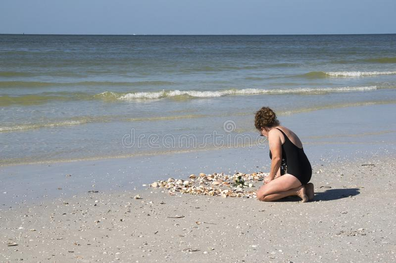 Woman collecting shells in the surf in the Gulf of Mexico royalty free stock photos