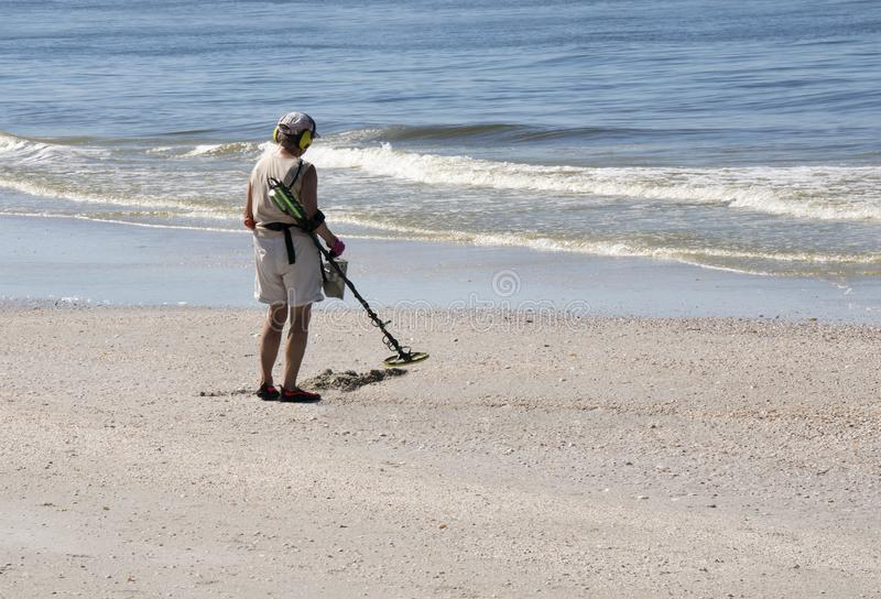 Woman with metal detector on St. Pete Beach, Florida. St. Pete Beach, Florida, October 29, 2018: A senior woman walks the beach with a metal detector searching stock photography