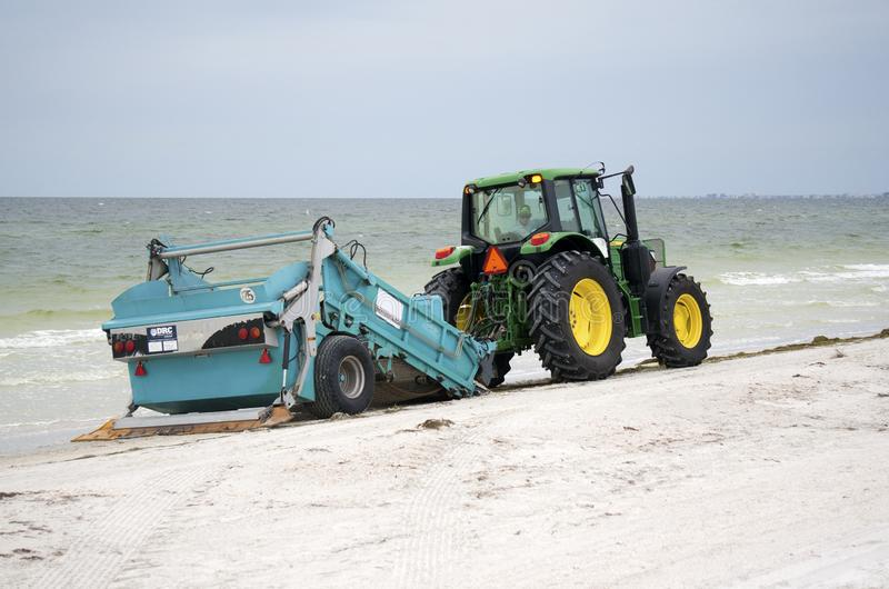 Beach cleaner on the Gulf of Mexico at St. Pete Beach, Florida. St. Pete Beach, Florida, October 23, 2018: A tractor pulling a beach cleaning machine moves royalty free stock image