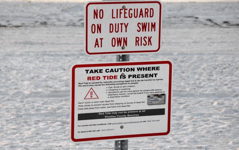 Red tide and rip current warning signs at St. Pete Beach, Florida. St. Pete Beach, Florida, October 24, 2018: Warning signs for red tide and rip currents are royalty free stock image