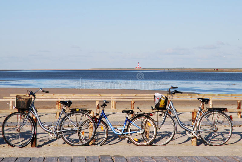 St. Peter Ording. Bicycles at the beach of St. Peter-Ording, Germany, with Westerhever lighthouse royalty free stock images