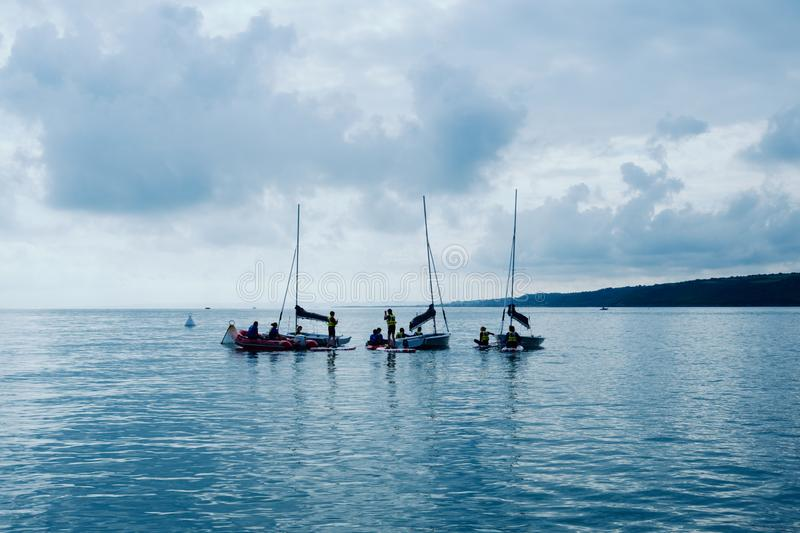 sailing school for kids practicing at the bay with calm flat water and little wind stock photos
