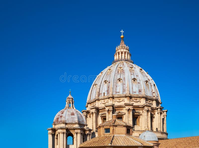 St. Peter`s Basilica in Rome, Italy. Closeup on cupola of St. Peter`s Basilica in Rome with blue sky, Italy, text space stock photo