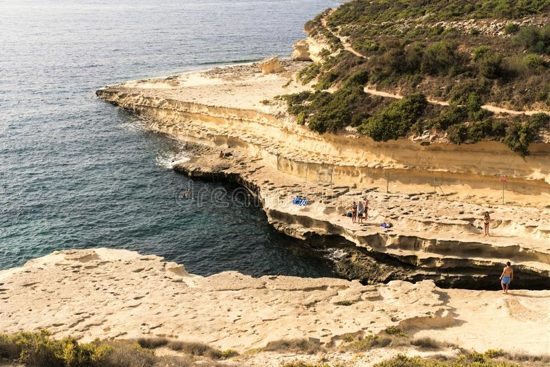 St. Peter`s Bay, Malta, August 2019. View of steep banks and sunbathing people. stock image