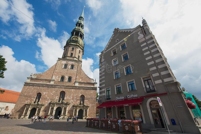 St. Peter`s church and historical building on a sunny summer day in downtown Riga, Latvia. Riga, Latvia - August 04, 2009: St. Peter`s church and historical royalty free stock photography
