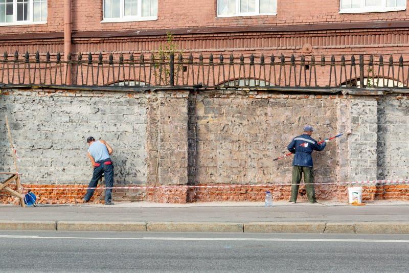 St Petersburg, federação de russo 16 de agosto de 2018: trabalhadores que reparam uma cerca do tijolo fotografia de stock royalty free