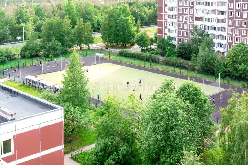 ST PETERSBURG, RÚSSIA - 16 DE JUNHO DE 2018 crianças que jogam no campo de futebol perto da escola foto de stock royalty free