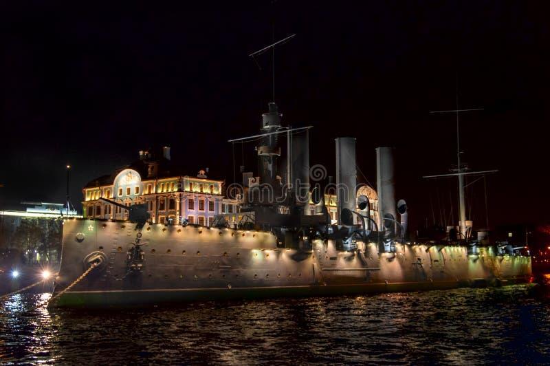 St Petersburg, Rússia, o 17 de outubro de 2018 - cruzador da Aurora com iluminação da noite no cais no rio de Neva imagens de stock