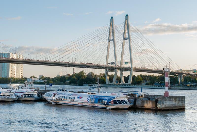 St Petersburg Rosja, Wrzesień, - 5, 2017: Trwanie hydrofoil łodzie przy rzecznym nabrzeżem z kablowym mostem w Petersburg, R fotografia royalty free