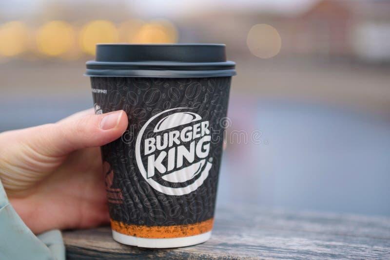 St Petersburg, RUSIA - 18 de diciembre de 2018: café Burger King en la taza de papel en mano femenina en fondo borroso de la ciud imagen de archivo libre de regalías