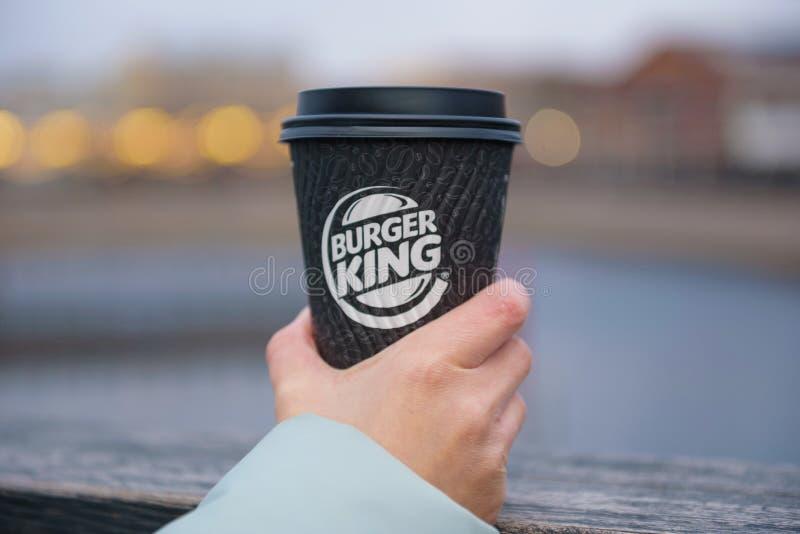 St Petersburg, RUSIA - 18 de diciembre de 2018: café Burger King en la taza de papel en mano femenina en fondo borroso de la ciud foto de archivo libre de regalías