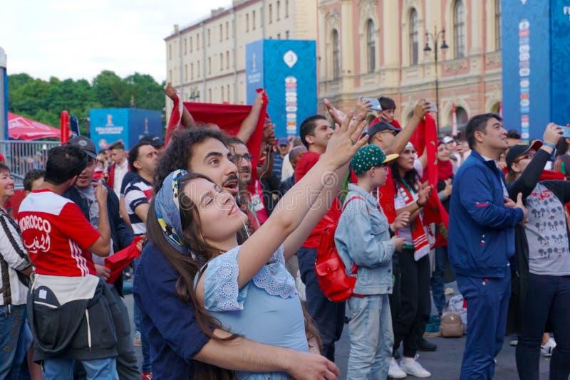 ST PETERSBURG, RUSIA - 15 DE JUNIO DE 2018: Un par joven hace el selfie en la zona de la fan del mundial 2018 de la FIFA del fest imagen de archivo libre de regalías