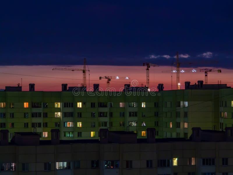 St. Petersburg, Rusland - Juli 24, 2018: Verscheidene bouwkranen op de achtergrond van kleurrijke zonsonderganghemel stock fotografie
