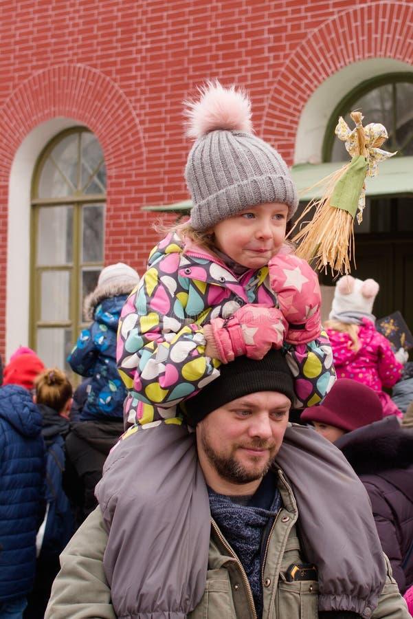 St. Petersburg, Rusland, 10 Maart, 2019 Een mens met een kind op zijn schouders op de winter van vakantiedraden stock foto