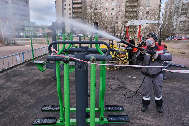 Communal service workers spray a disinfectant solution against the COVID-19 virus on a public sports ground in a residential quart. St. Petersburg, Russia royalty free stock photography
