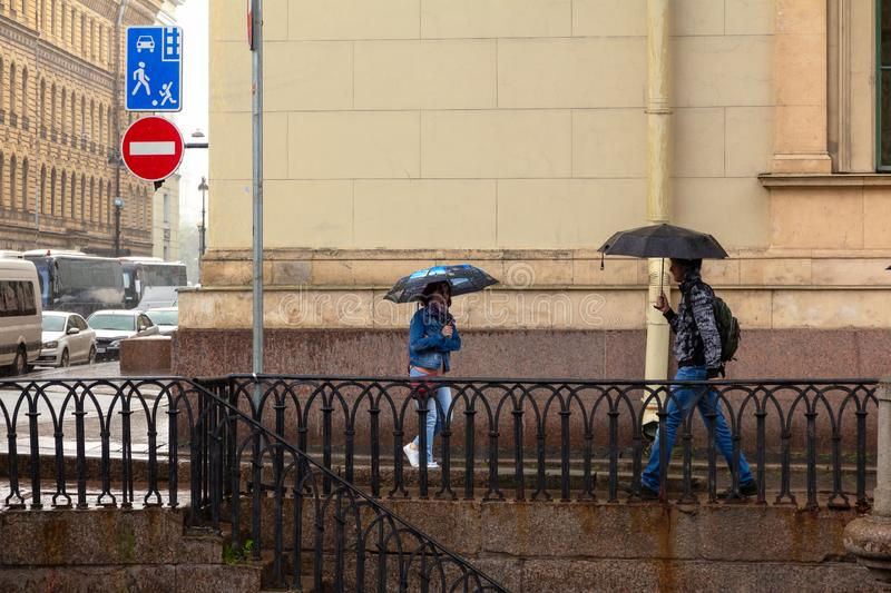 people with umbrellas are walking in the rain along the granite embankment near the Hermitage. Tourists in rainy weather royalty free stock images