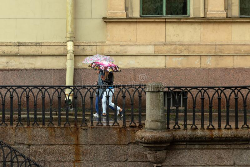 People under umbrellas walk along the granite promenade in the rain stock photography