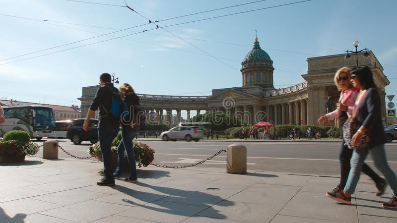 People walk on the Nevsky street on the Kazan Cathedral background in the summer, car tra. ST. PETERSBURG, RUSSIA - AUGUST 9, 2017: People walk on the Nevsky stock photography